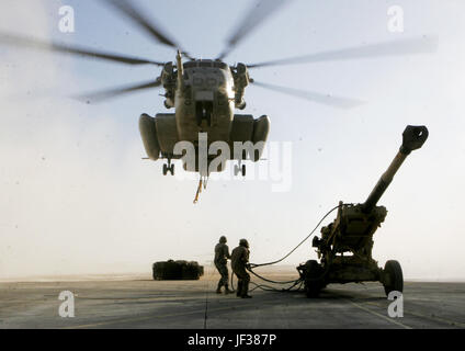 061129-M-8213R-004  Marines prepare to attach a sling fastened to a M198 Medium Howitzer onto a U.S. Marine Corps CH-53E Super Stallion helicopter in Al Asad, Iraq, on Nov. 29, 2006,   The Super Stallion, from Heavy Marine Helicopter Squadron 465, 3rd Marine Aircraft Wing (Forward), will airlift the howitzer to Barwana, Iraq.  DoD photo by Gunnery Sgt. Michael Q. Retana, U.S. Marine Corps.  (Released)