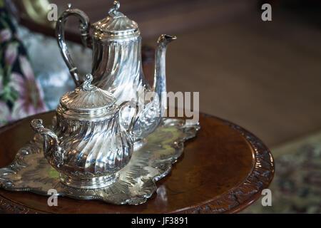 Vintage luxury silver dishware, tea set on wooden table - Stock Photo