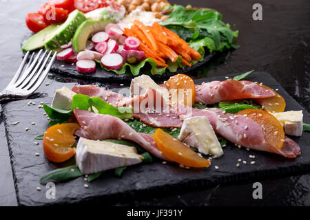Two different salads om black stone slate. Vegan salad. Meat salad. Salad with ham jamon serrano, camembert, melon, - Stock Photo