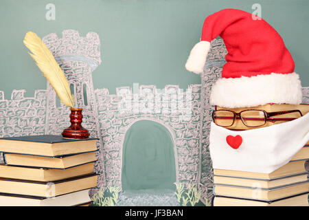 Unusual Santa Claus from books before blackboard with drawing chalk of castle - Stock Photo