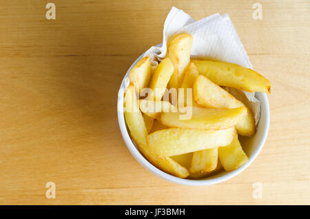 Overhead shot of a bowl of chips (french fries) on a wooden table.  Copy space to left. - Stock Photo