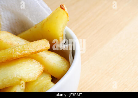 Close up (macro) of a bowl of chips (french fries) nestling on absorbent paper in a white bowl.  Wooden table surface - Stock Photo