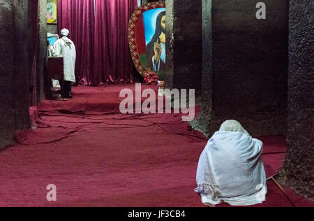 Lalibela, Ethiopia, A faithful and a priest in the Bet Mariam Orthodox churhc - Stock Photo