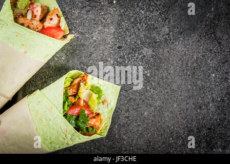 Mexican food. Healthy eating. Wrap sandwich: green lavash tortillas with spinach, fried chicken, fresh greens salad, - Stock Photo