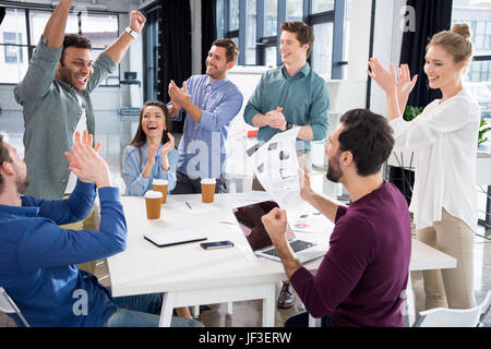 business team celebrating success together on workplace in office, young professional group concept - Stock Photo