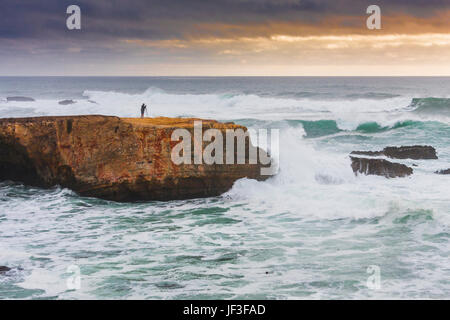 Photographer on cliff at Point Arena on the rocky pacific coast of northern California. Storm coming in from the - Stock Photo