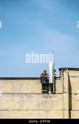 A worker fixing a cellular radio antenna on the top of the building. Blue sky background - Stock Photo