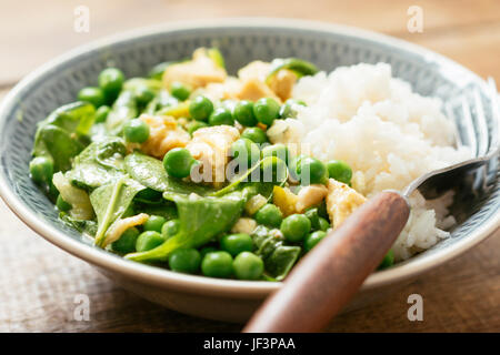 Vegan Thai Green Curry with Soy Protein, Spinach and Fresh Garden Peas - Stock Photo
