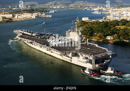 The aircraft carrier USS Ronald Reagan (CVN 76) is aided by harbor tugs as it enters Pearl Harbor, Hawaii. DoD photo - Stock Photo