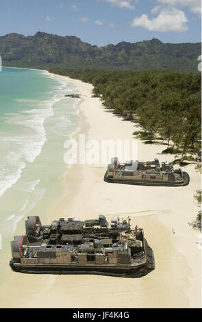 U.S. Navy Landing Craft, Air Cushioned vessels (LCAC's), land on the beach to offload equipment and Marines. DoD - Stock Photo