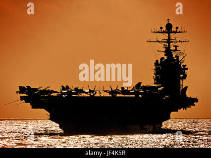The Nimitz-class aircraft carrier USS George Washington against an orange sky. U.S. Navy photo by Photographer's - Stock Photo