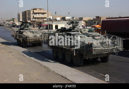 041004-A-0392G-016 U.S. Army soldiers patrol in Stryker armored wheeled vehicles during a search for criminals and - Stock Photo