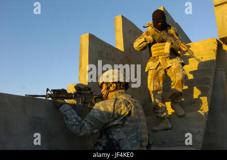 061111-A-2519G-124  U.S. Army Staff Sgt. Coriey Burkman and an Iraqi army soldier clear the roof of an Iraqi home - Stock Photo