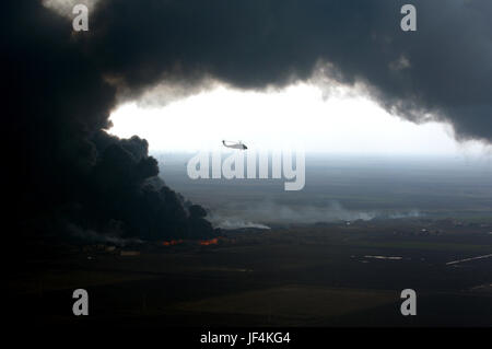 051227-A-7359K-128  A plume of smoke surrounds a U.S. Army UH-60 Black Hawk helicopter as soldiers of the 101st - Stock Photo