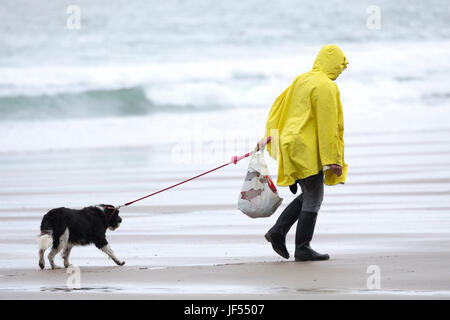 A person walking a dog on a lead along the pristine and dog friendly beach during a summer shower wearing a yellow - Stock Photo