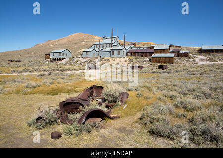 The deteriorating metal frame of an antique vehicle partially buried in the ground near the stamp mill in Bodie - Stock Photo