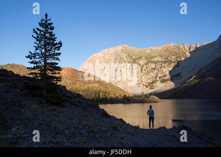 A visitor to Yosemite National Park stands on the rocky shore of Ellery Lake. - Stock Photo