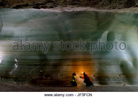 Scientists examine the thick bed of ice for samples inside Eisriesenwelt Eishoehle in Werfen, Austria. - Stock Photo