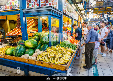 Colourful fruit stall with attractive display of bananas, melons and fruits in the covered Central Market Hall (Vasarcsarnok), - Stock Photo