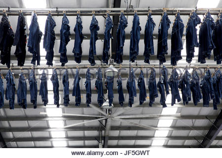 Jeans move along a large conveyor belt that naturally dries items at a modern denim factory. - Stock Photo