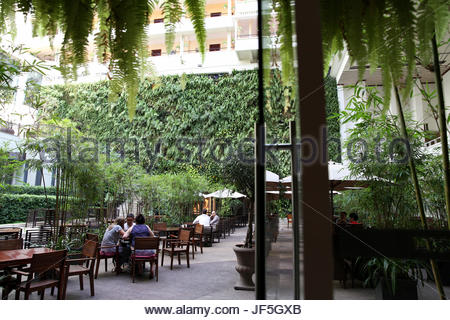 The interior garden at the Rex Hotel in downtown Ho Chi Minh City. - Stock Photo