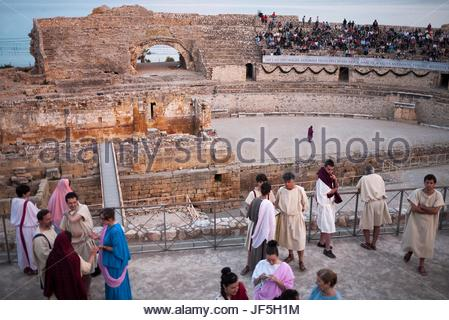 Actors dressed in costumes of the Roman Empire in the amphitheater of Tarragona at a performance. - Stock Photo