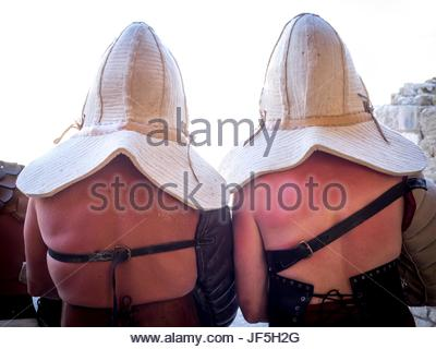 Extras dressed in Roman gladiator costumes waiting before a historical reenactment. - Stock Photo