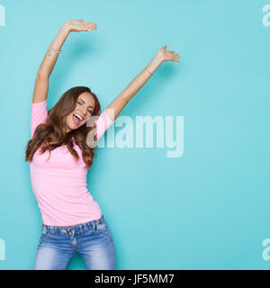 Happy beautiful young woman in pastel pink shirt shouting with arms raised and winking. Three quarter length studio - Stock Photo