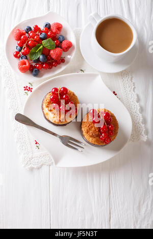 Coconut muffins with berries and coffee with milk close-up on the table. vertical view from above - Stock Photo