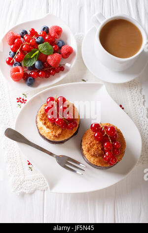 Coconut muffins with currants and coffee with milk close-up on the table. vertical view from above - Stock Photo