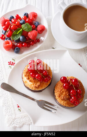 Delicious breakfast, coconut muffins, berries and coffee with milk close-up on the table. vertical view from above - Stock Photo