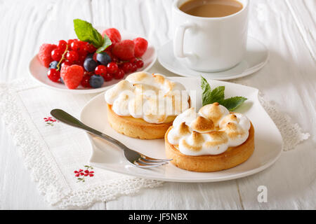 Lemon tart with meringue and berry mix, coffee on the table. close-up. horizontal - Stock Photo