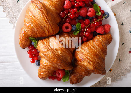 Golden croissants with fresh summer berries close-up on a plate. horizontal view from above - Stock Photo