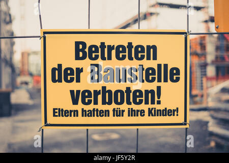 Yellow sign in german: Betreten der Baustelle verboten! Eltern haften für ihre Kinder! translation: entering the - Stock Photo