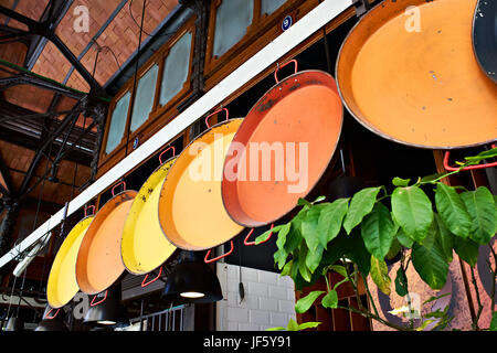 Metal color dishes for paella on sale in the market - Stock Photo