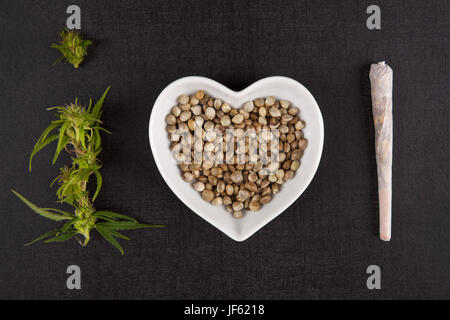 Healthy Marijuana medicine. Buds, seeds in heart shaped bowl and cannabis joint from above on black background. - Stock Photo