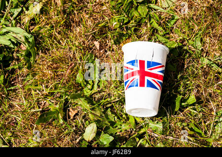An empty plastic cup printed with the Union Jack lying on grass. - Stock Photo
