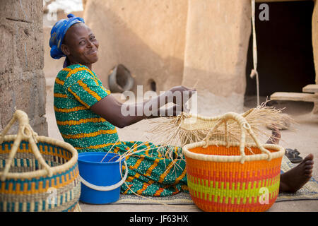 A woman weaves traditional straw baskets in Upper East Region, Ghana. - Stock Photo