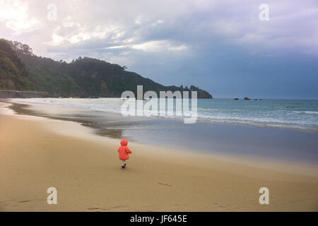 Baby girl on the coast of the sea: landscape of the ocean - Biscay bay - Stock Photo