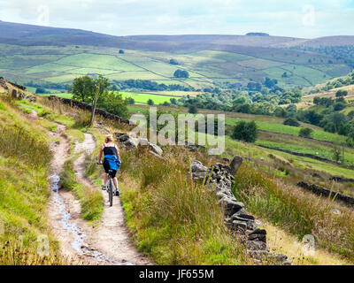 A woman cycling on a bridleway near Three Shires Head in the Peak District National Park - Stock Photo