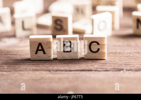 Alphabet letters on wooden pieces collected in word abc - Stock Photo