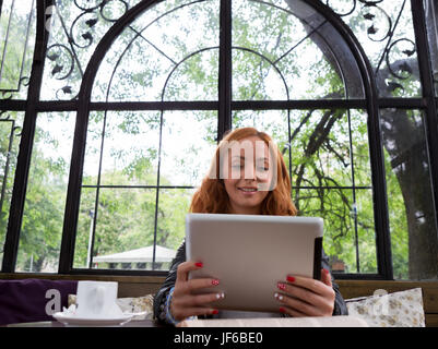 Pretty girl posing with a tablet in cafe - Stock Photo