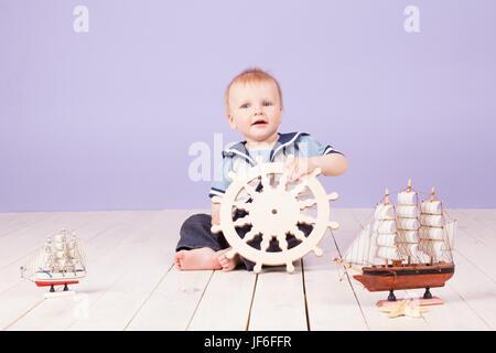 a little boy dressed as a sailor captain of ship - Stock Photo