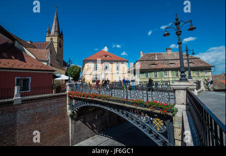 Liar's Bridge over Ocnei Street on Small Square in Old Town of Sibiu, Romania. View with former Crown of Hungary - Stock Photo