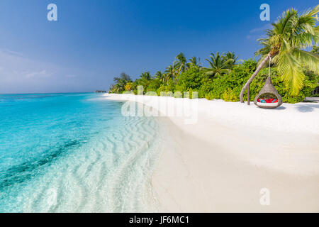Perfect tropical beach. Romantic hammock or swing on white sand beach and palm trees under blue sky. Inspirational - Stock Photo