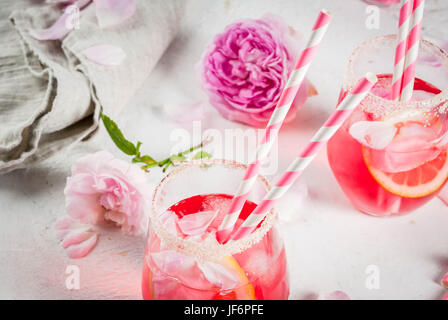 Summer refreshment drinks. Light pink rose cocktail, with rose wine, tea rose petals, lemon. On a white stone concrete - Stock Photo