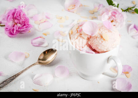 Summer refreshing desserts. Vegan diet food. Ice cream with rose petals and slices of almond, in white serving bowls, - Stock Photo