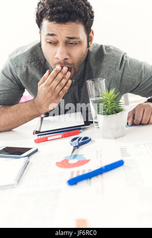 young tired casual businessman sitting at table in office, business establishment - Stock Photo