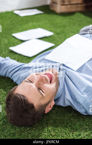 side view of smiling businessman lying on grass with documents, business establishment  concept - Stock Photo