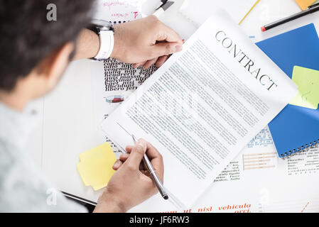 Overhead view of businessman holding contract above table with papers - Stock Photo